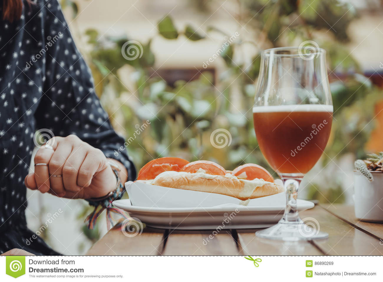 Person Drinking Beer And Eating un hot dog
