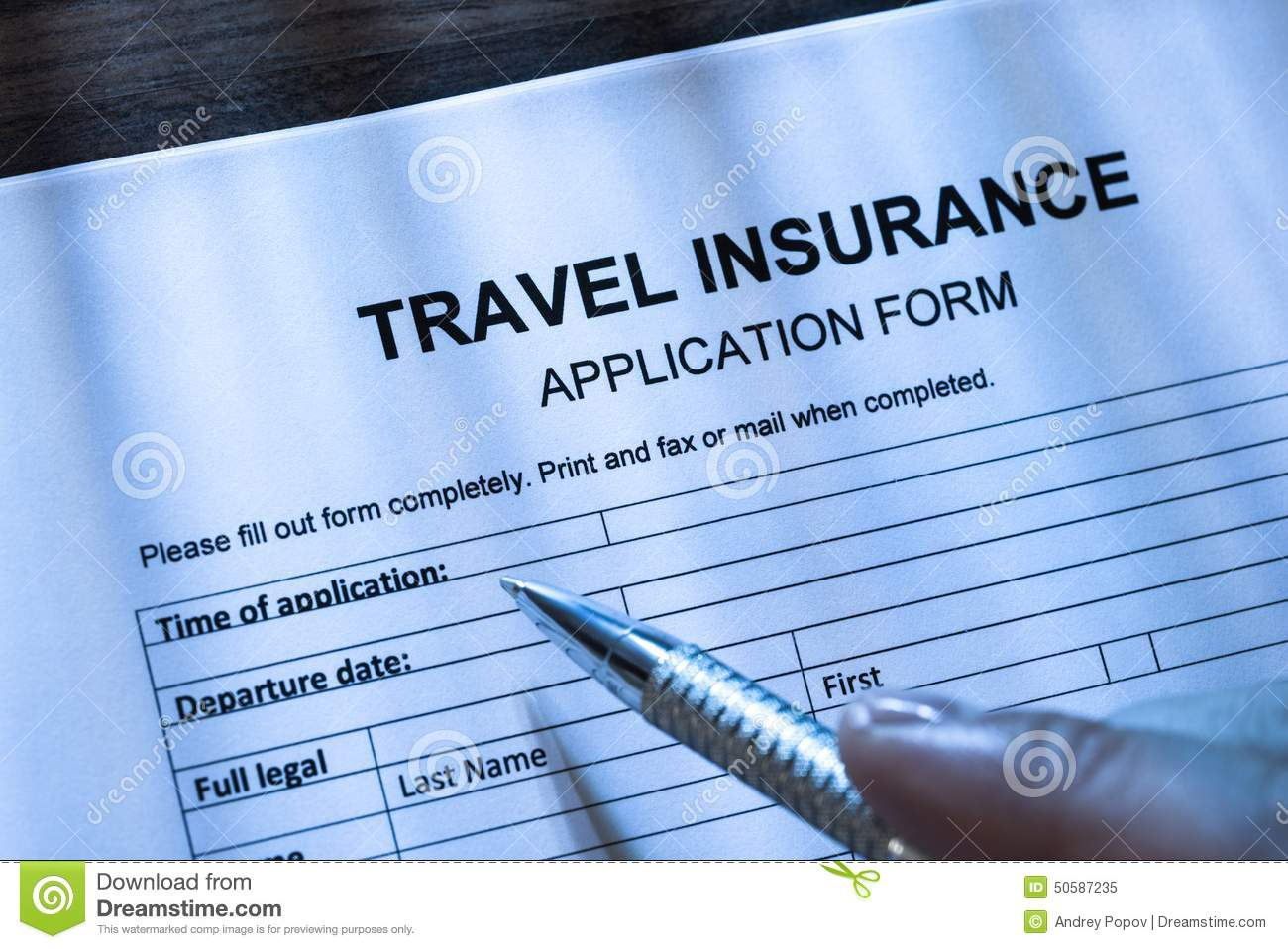 person filling travel insurance application form stock photo person filling travel insurance application form