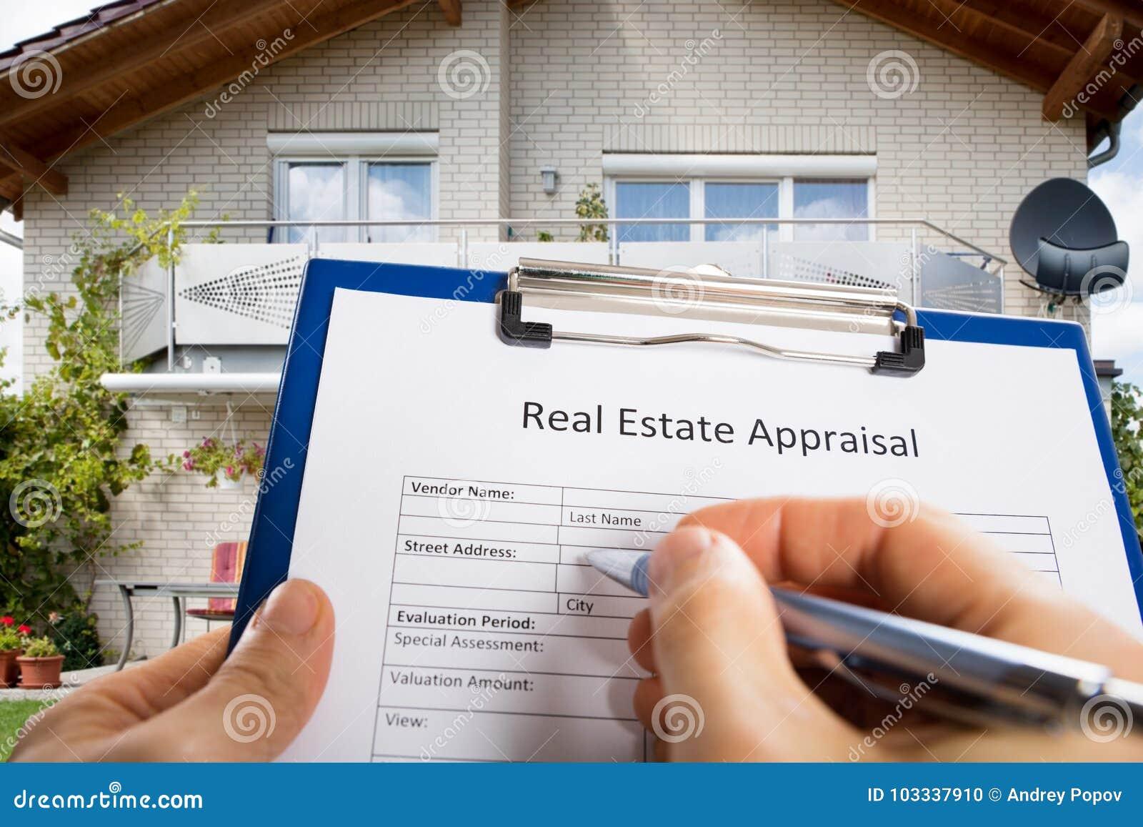Person Hand Filling Real Estate värderingdokument