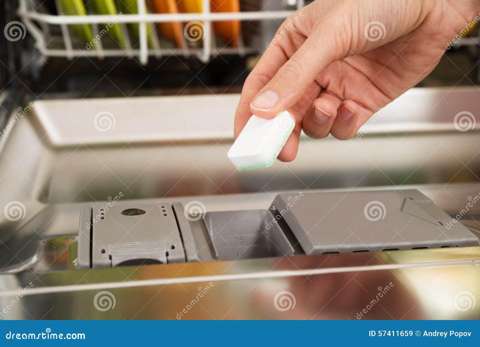 Person Hands Putting Dishwasher Tablet in der Spülmaschine Box