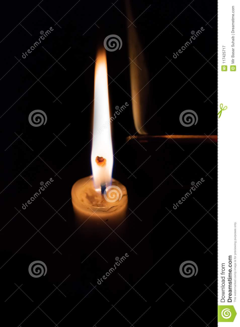Person lighting a candle with a matchstick. Smoke from an extinguished matchstick