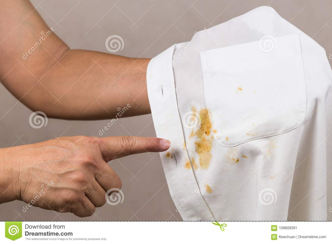 Person Pointing To Spilled Curry Stain On White Shirt Stock Image