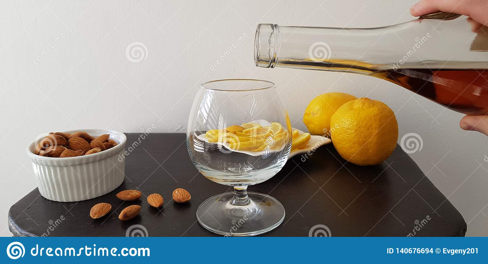 Person pours brandy into a glass
