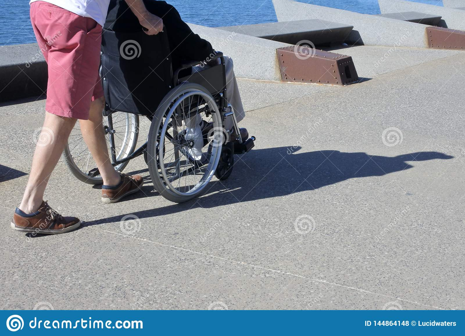 Person pushing a senior adult man on a wheelchair outdoors