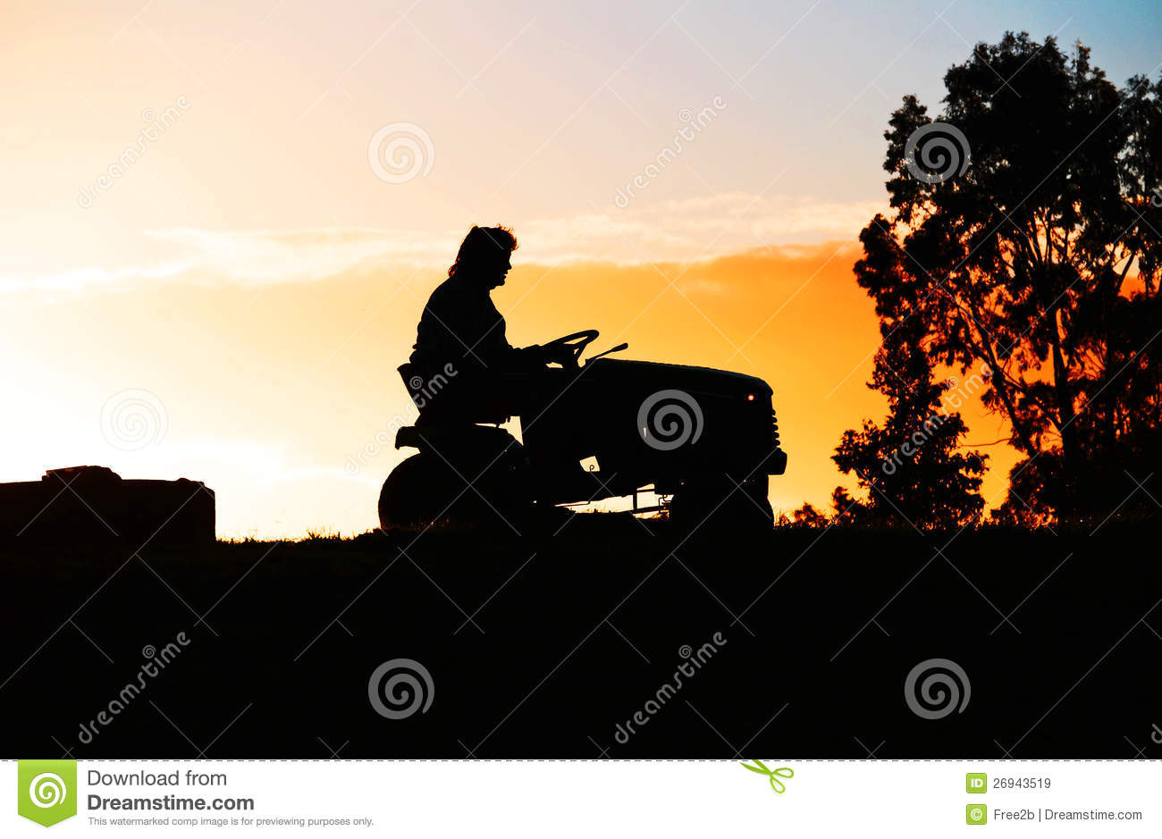 Person On A Ride On Lawn Mower On Farm At Sundown Stock