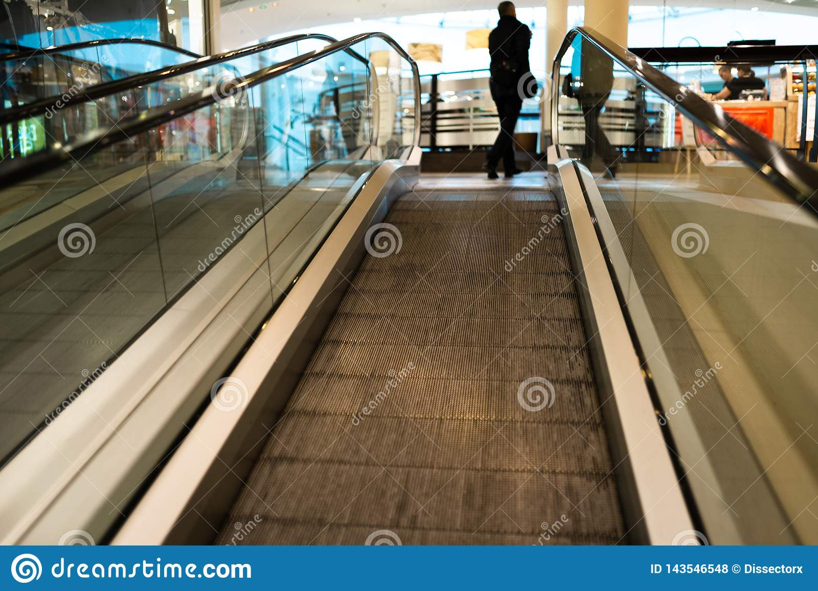 Person rush on escalator motion blurred in the background