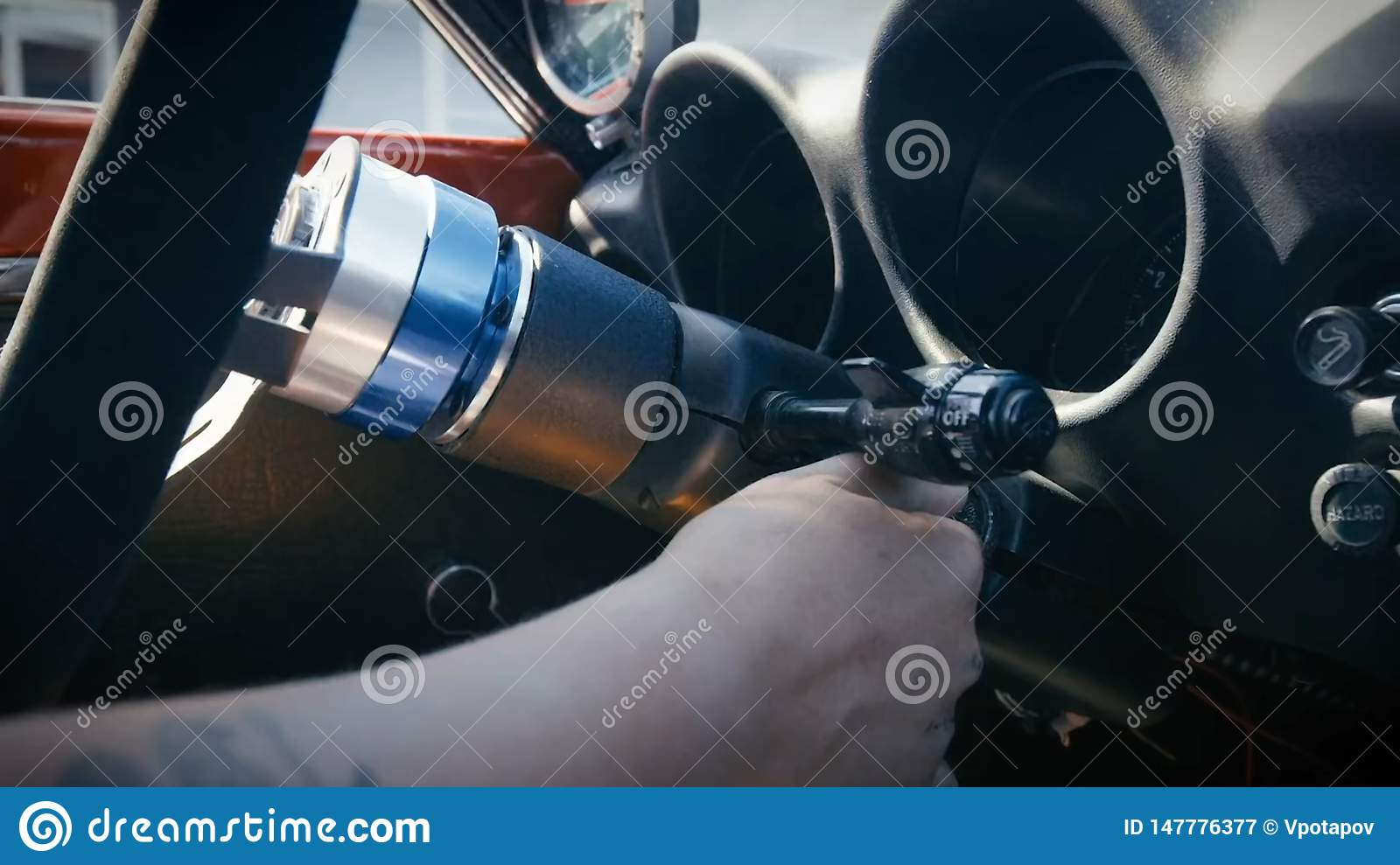 Person`s Hand Inserting Key To Start Car.