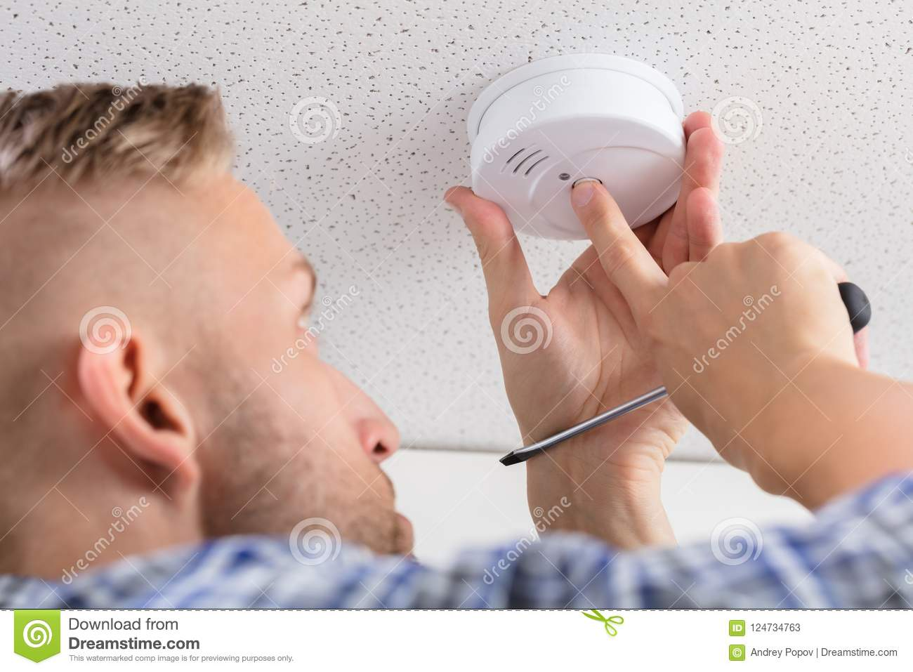 Person`s Hand Installing Smoke Detector On Ceiling