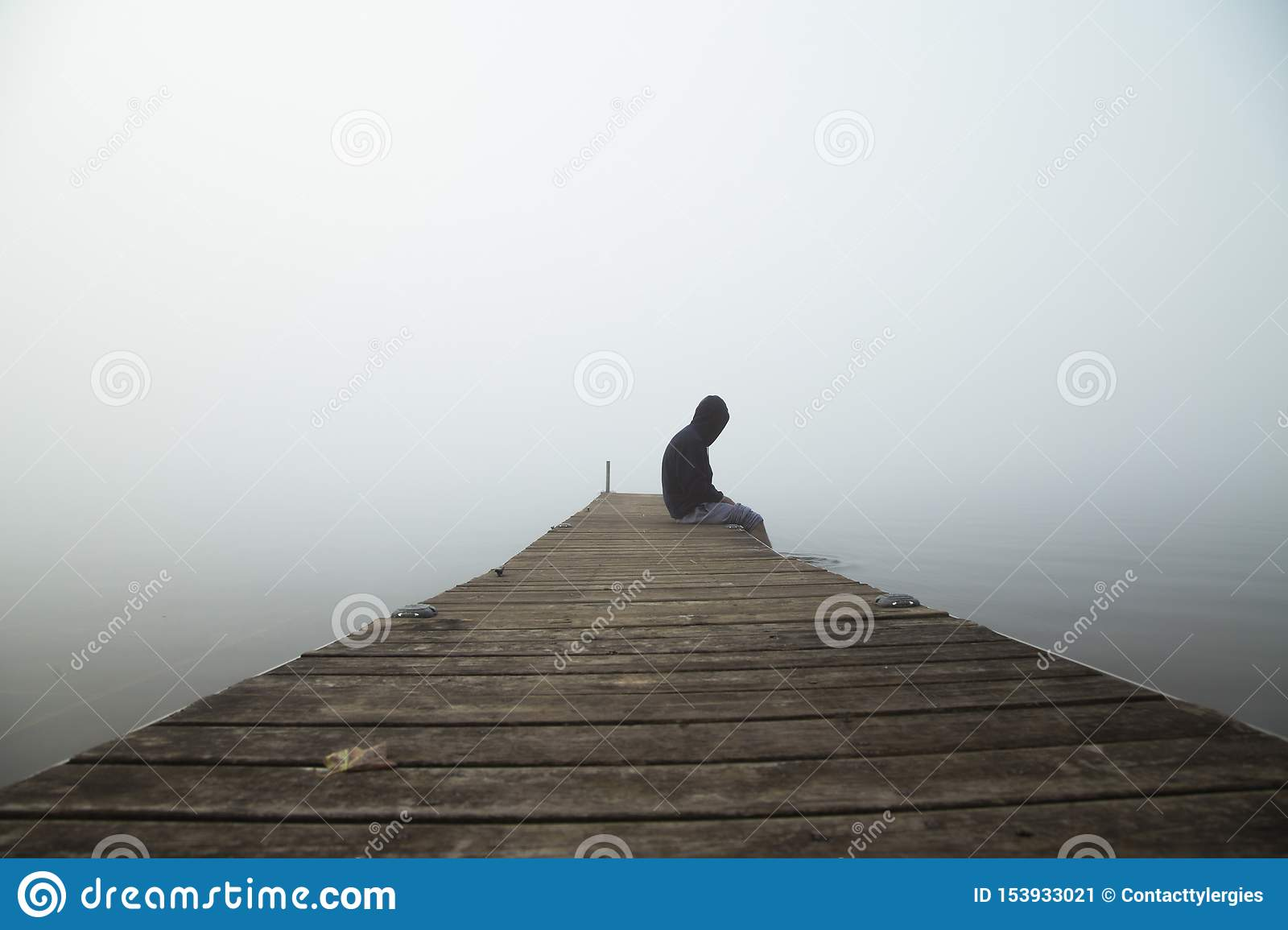 Person sitting on dock early morning with fog in the sky