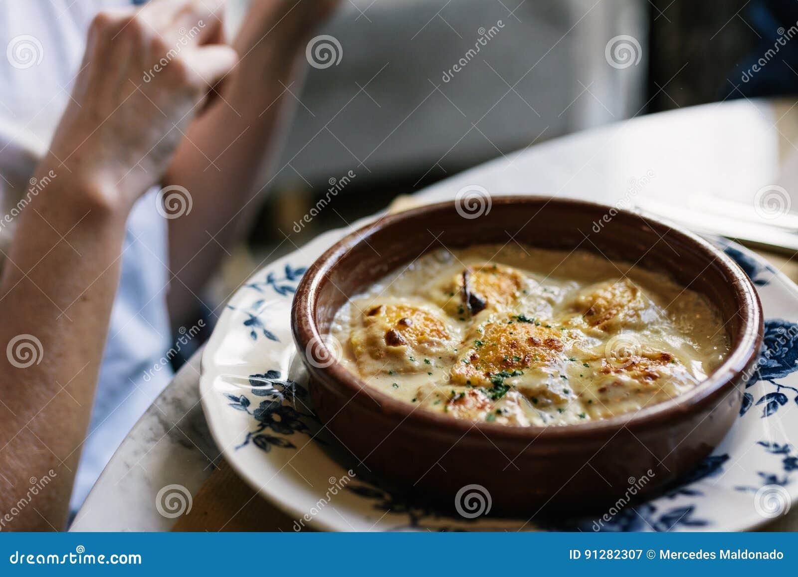 Person som äter raviolin med gratängost, i restaurang