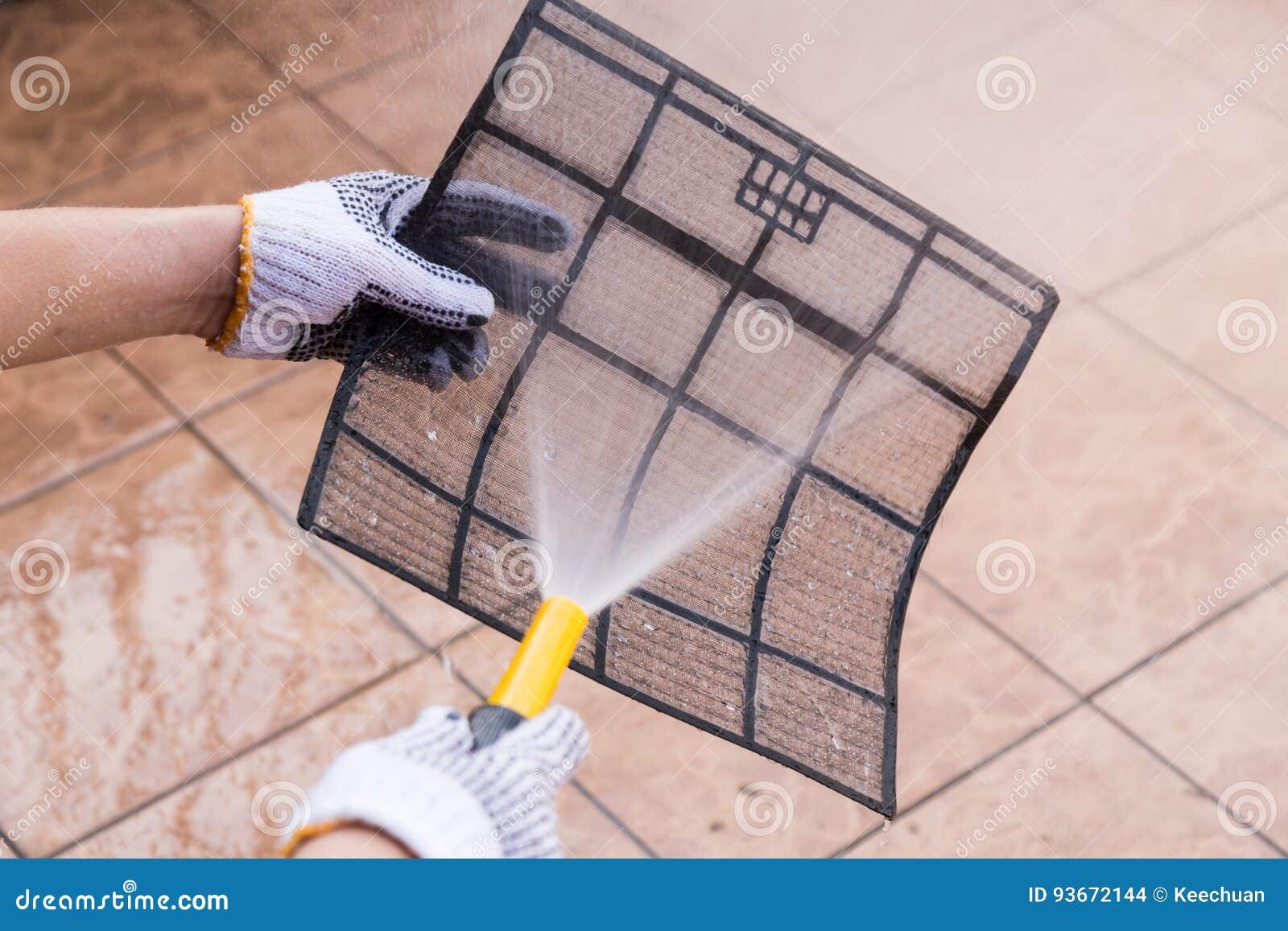 Person som besprutar vatten på luftkonditioneringsapparatfiltret för att göra ren damm