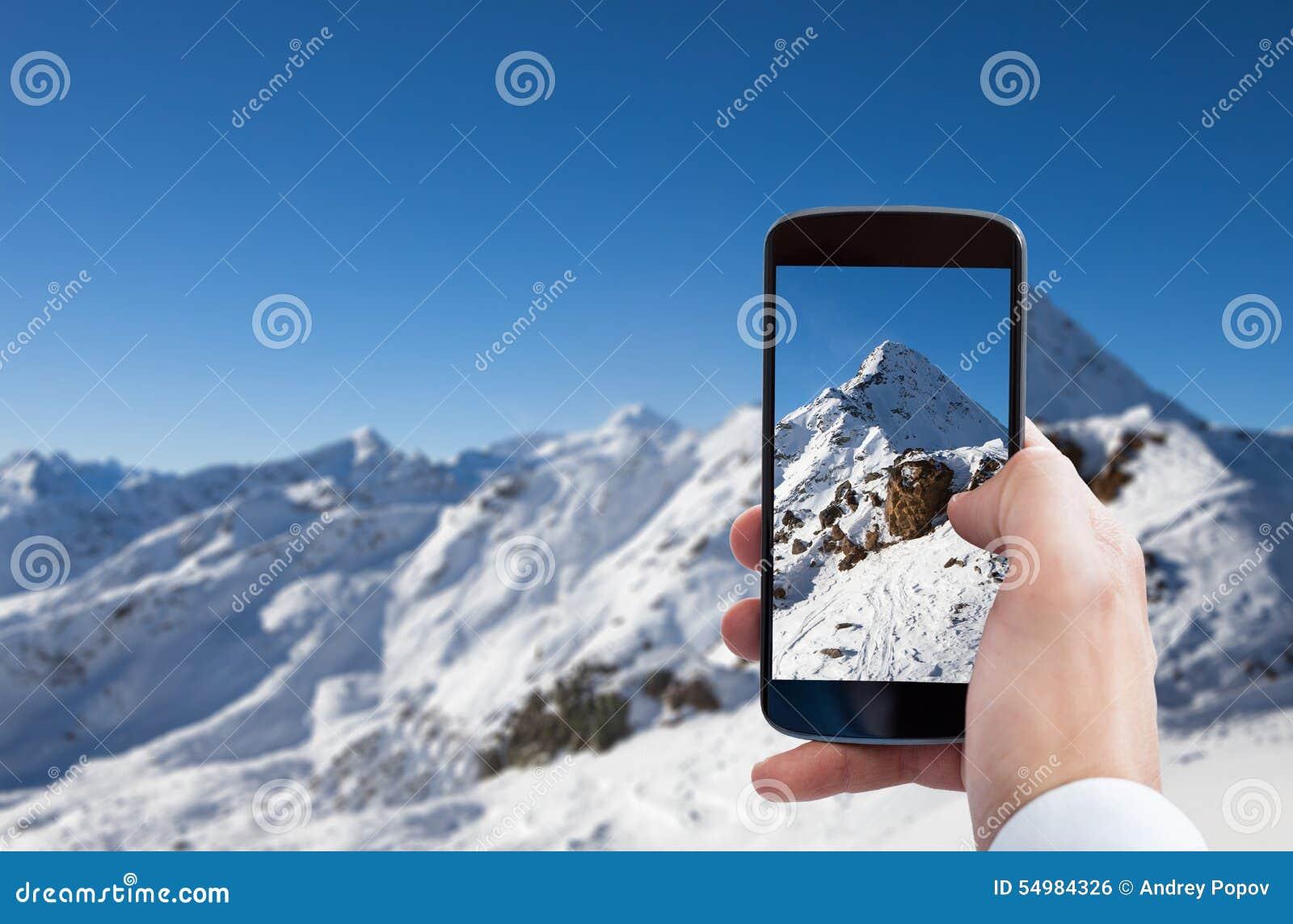 Person som fotograferar snöig berglandskap