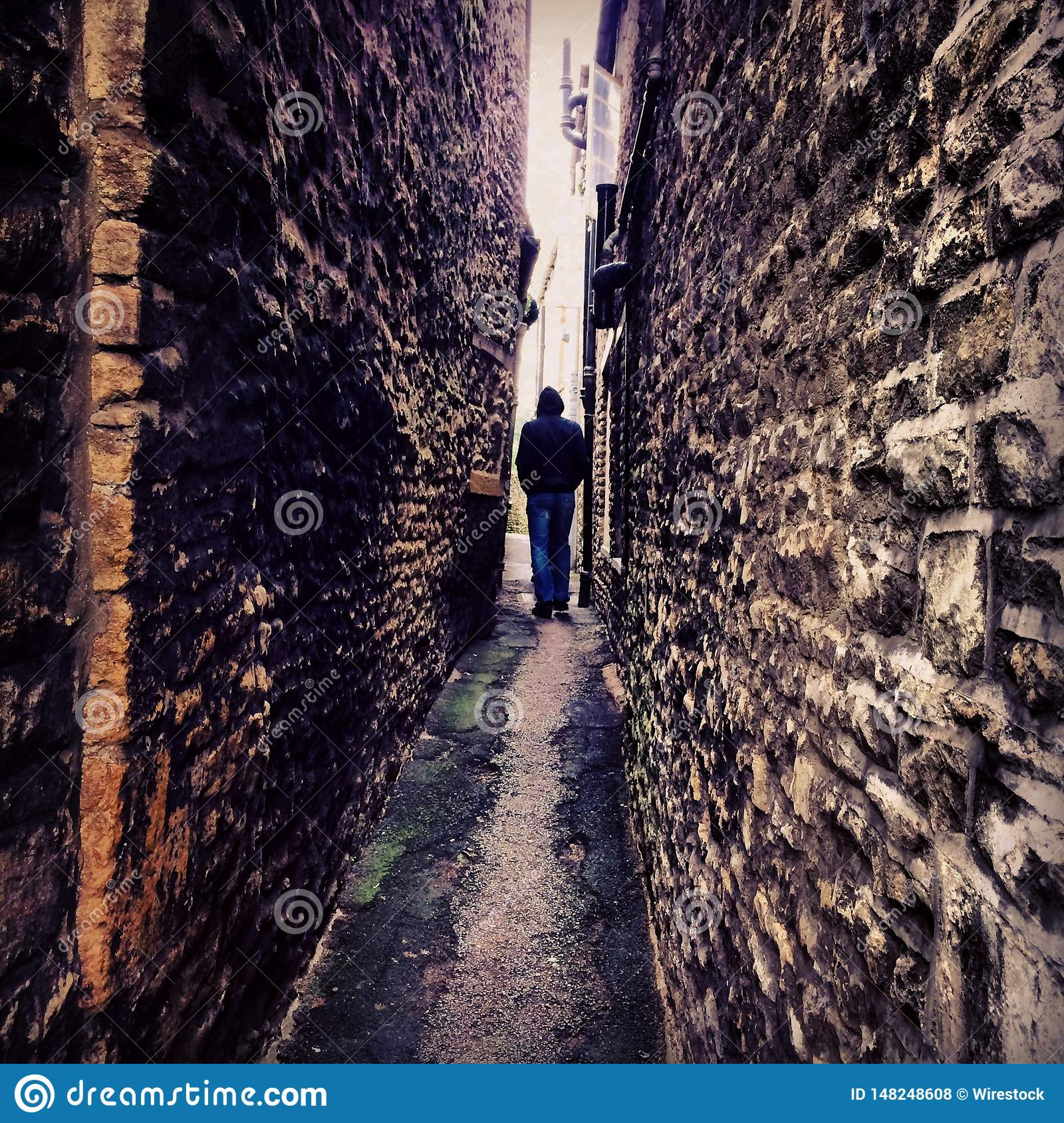 A person standing in a narrow pathway between two brick walls