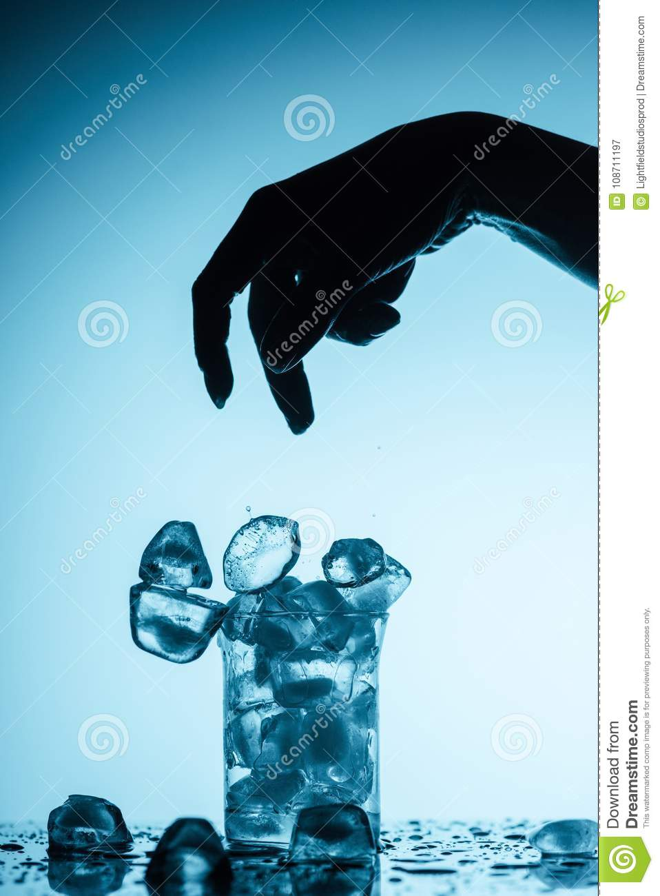 Person throwing ice cubes into glass