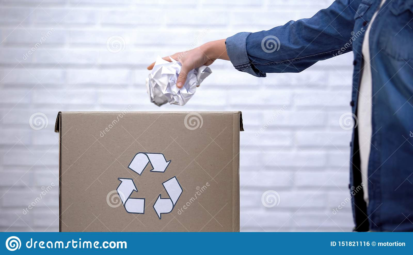 Person throwing paper into trash bin, waste sorting concept, recycling system