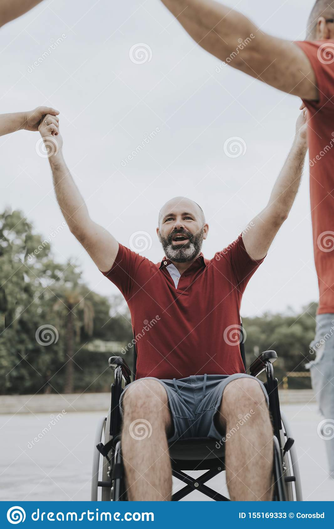 person in a wheelchair hands with his friends
