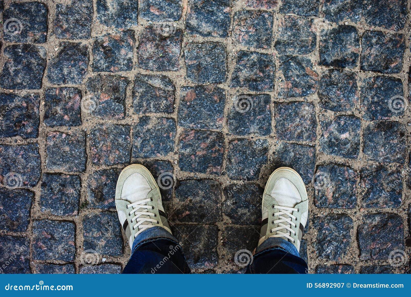 Persona adolescente in scarpe da tennis che stanno sulle pietre per lastricati
