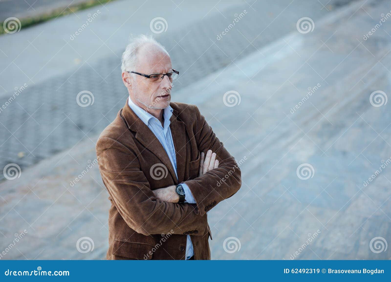 be3295517b573 Persona adulta con el pelo gris y haber vestido elegante de las lentes,  exterior en los pasos de un edificio de oficinas