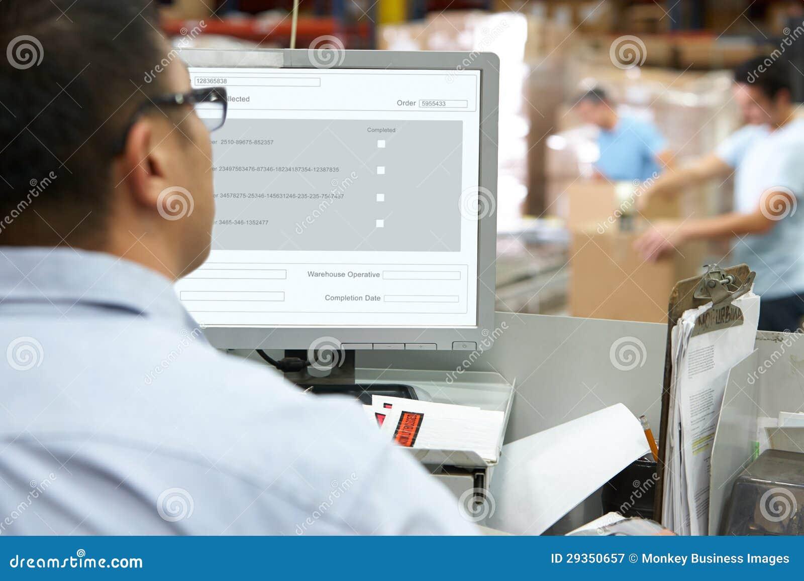 Persona al terminale di calcolatore elettronico nel magazzino di distribuzione