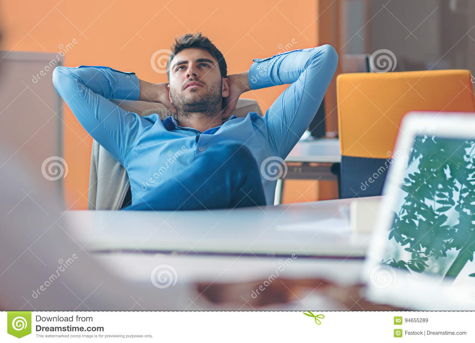 Persona caucásica del negocio que se sienta en manos que sueñan despierto de pensamiento de la oficina detrás de la cabeza