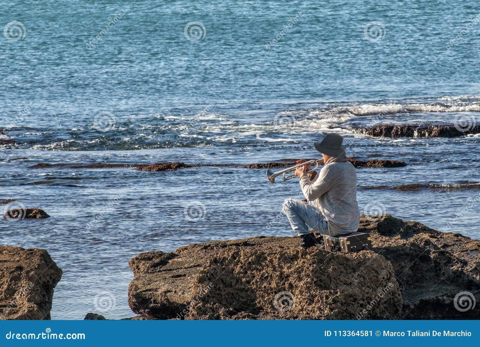 Persona che gioca il sassofono che si siede sulle rocce davanti ad un bello mare