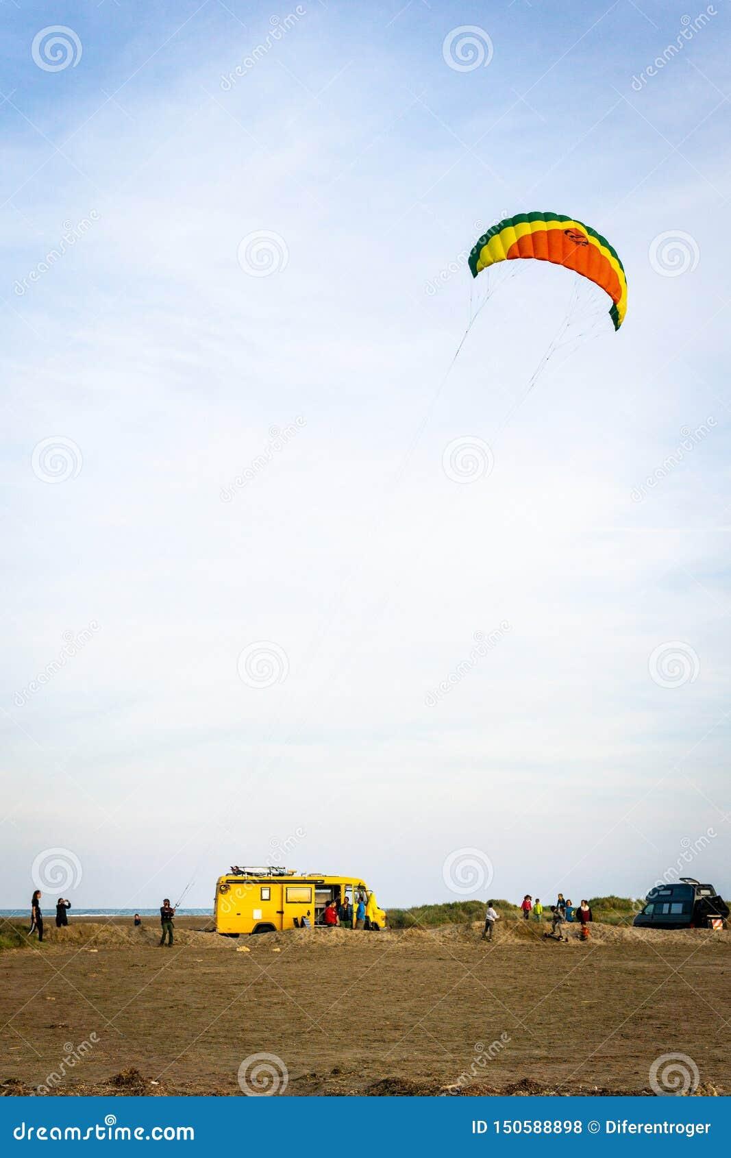 Persona che pilota un aquilone della spuma sulla spiaggia con i furgoni nei precedenti