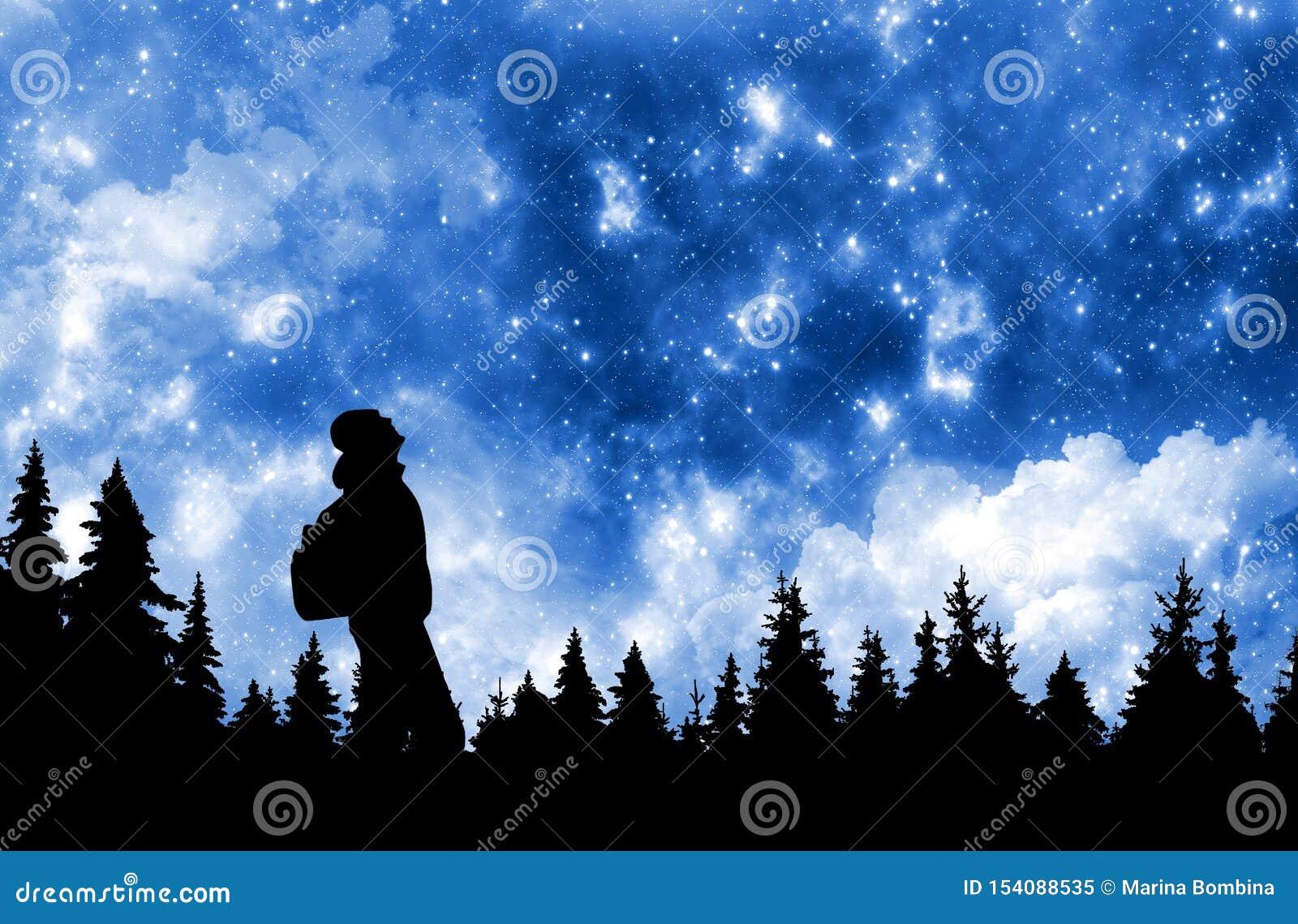 Persona con la mochila que mira las estrellas en cielo nocturno sobre el bosque del pino
