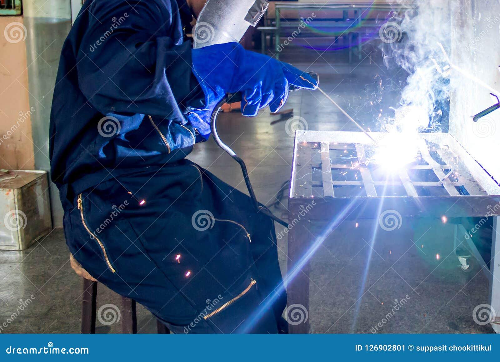Persona de funcionamiento sobre la máquina de la soldadura al acero del soldador