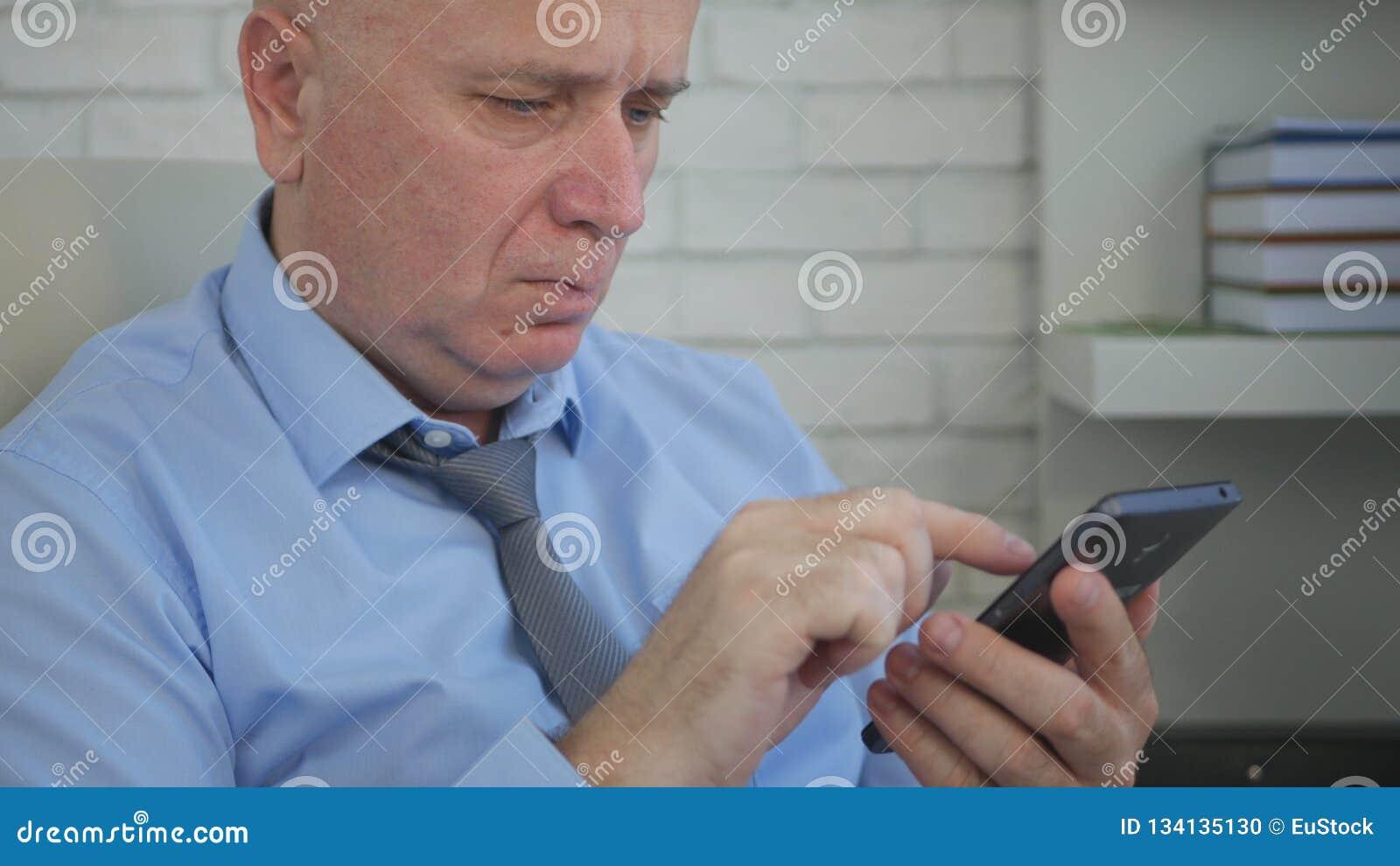 Persona di affari seria in testo della stanza dell ufficio facendo uso del telefono cellulare