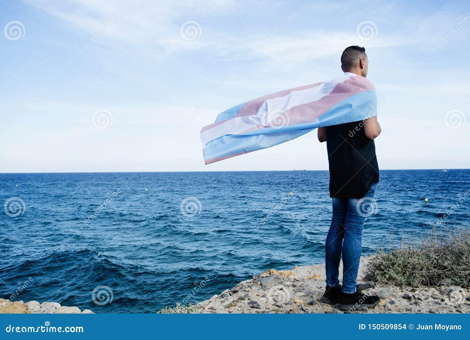 Persona joven con una bandera del orgullo del transexual
