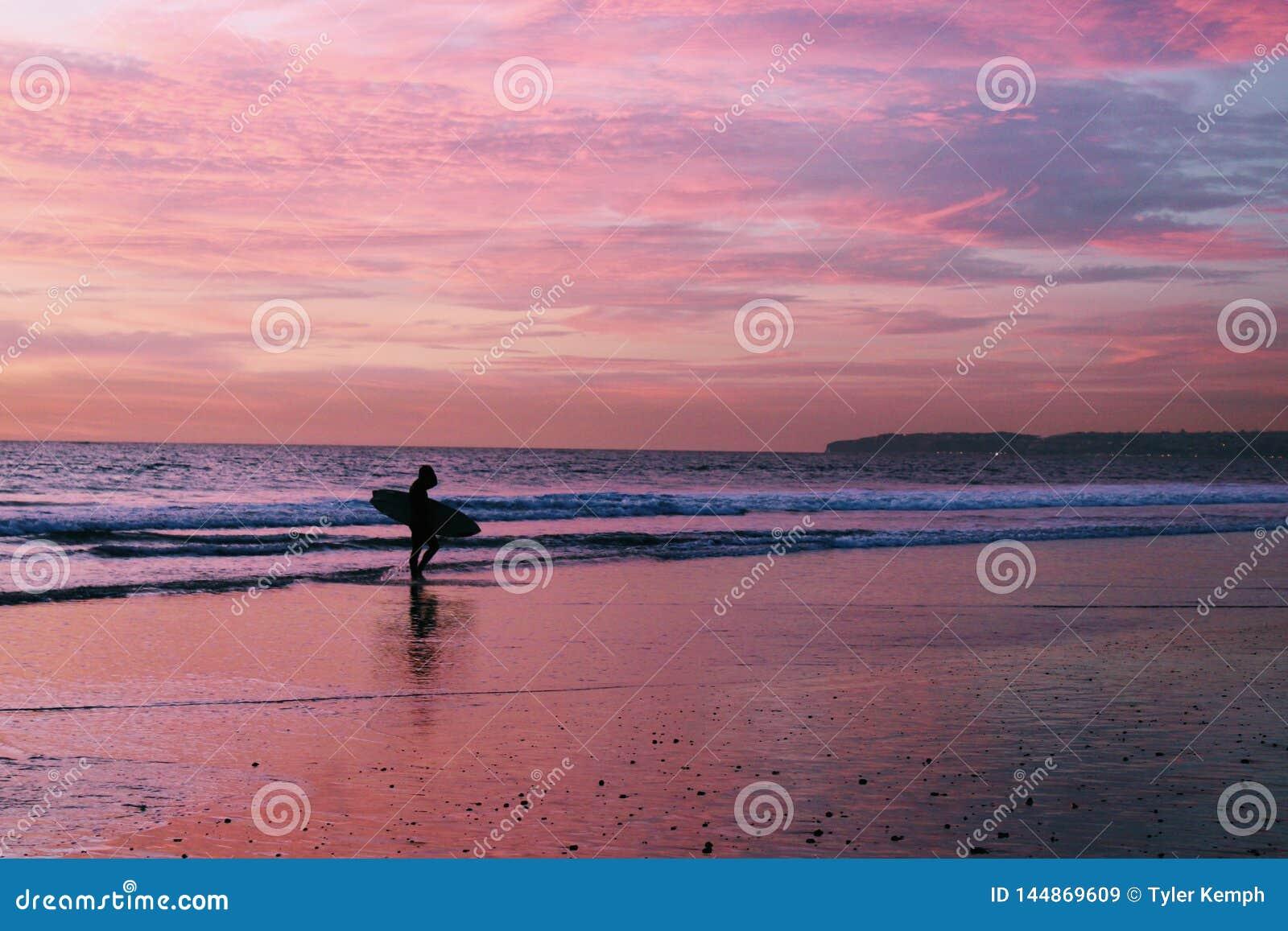 Persona que practica surf en la playa durante puesta del sol