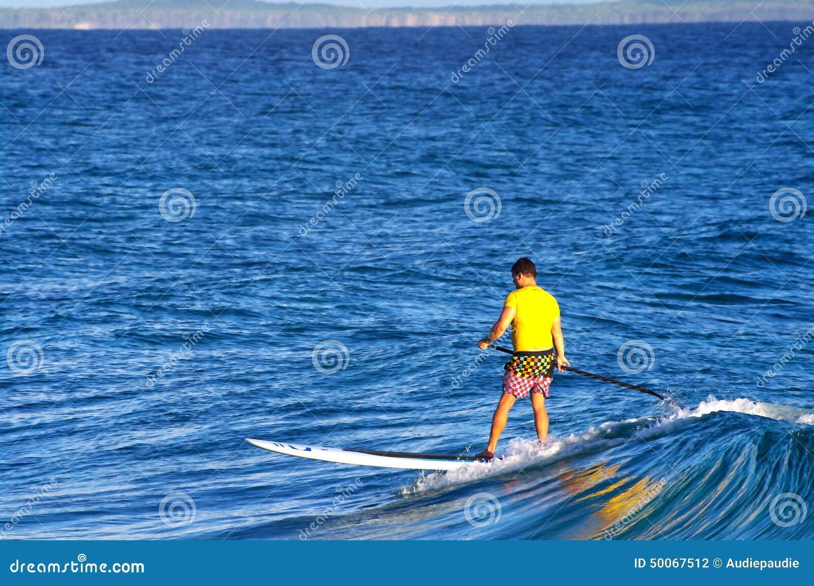 Persona que practica surf en un tablero de paleta de pie