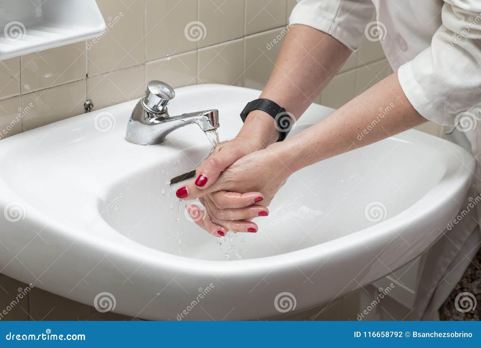 Lavabo Manos.Persona Que Se Lava Las Manos En Un Lavabo Blanco Foto De