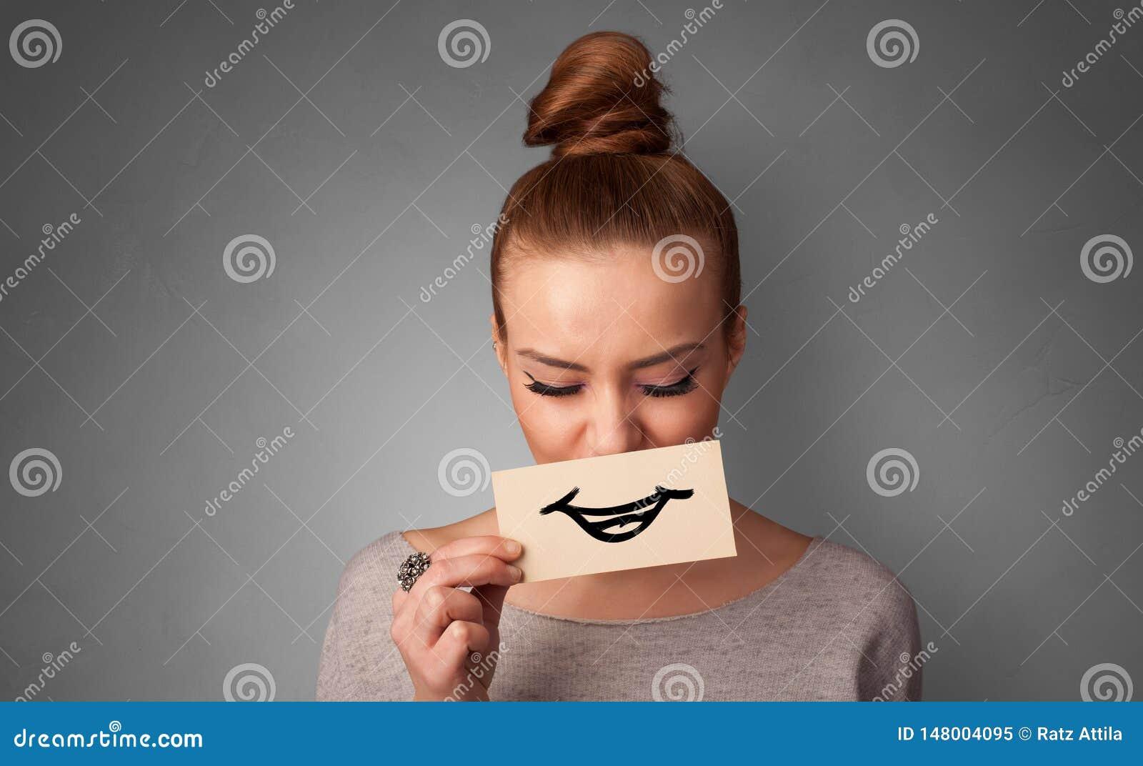 Persona que sostiene delante de su boca una tarjeta