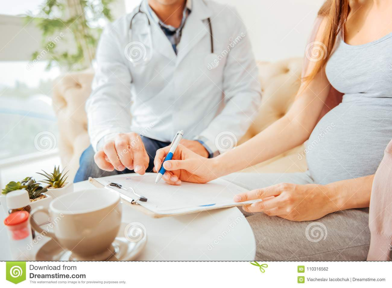 close up of pregnant woman filling medical form stock photo - image
