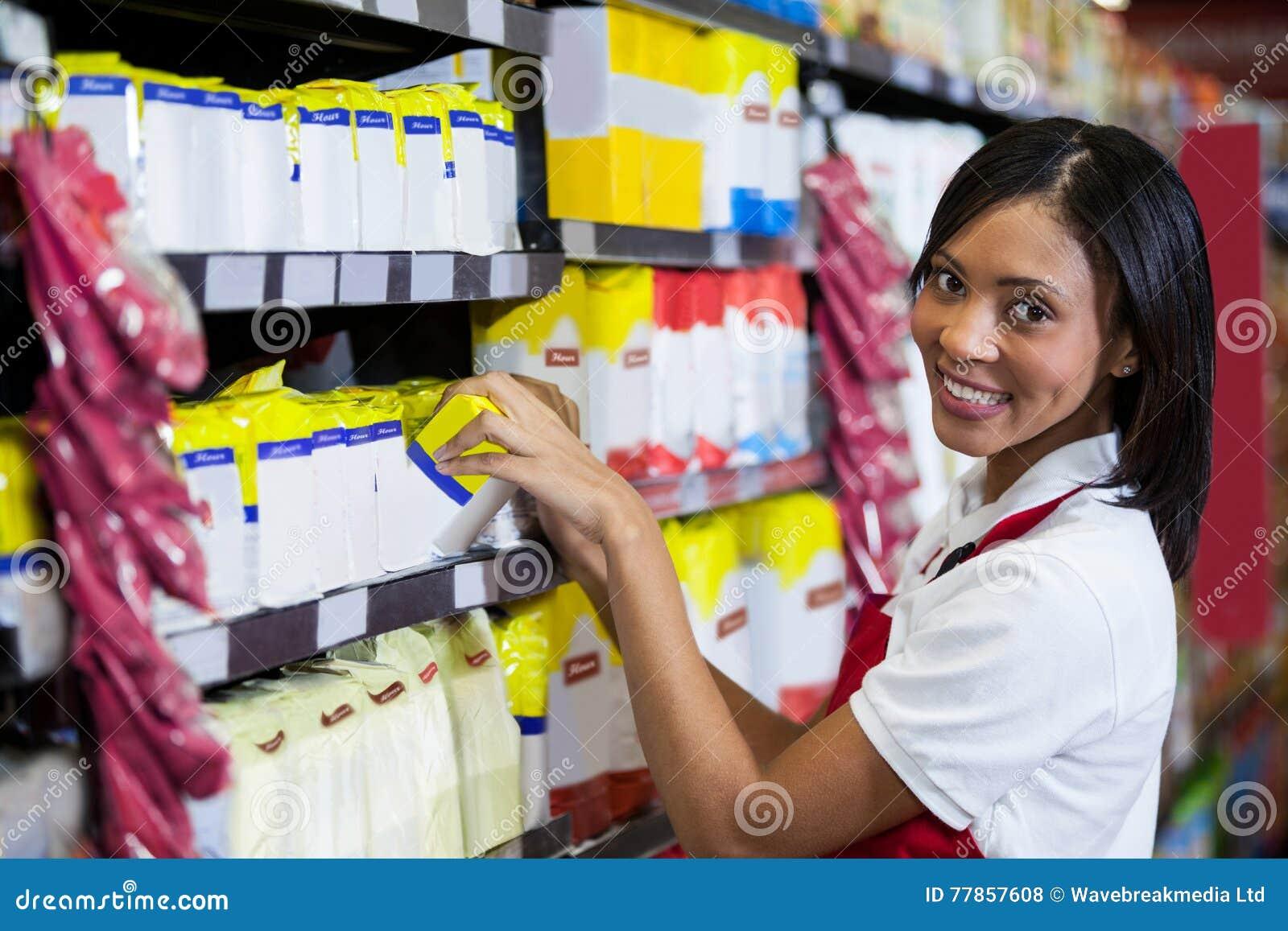 Personal femenino que arregla mercancías en la sección del ultramarinos