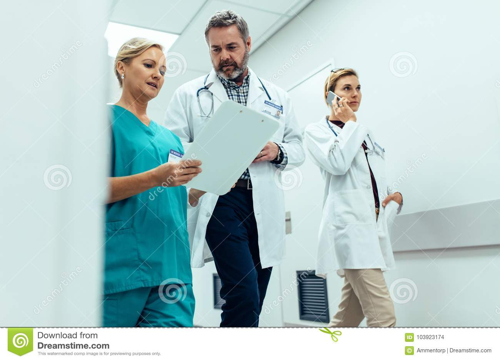 Personal hospitalario ocupado que discute en vestíbulo del hospital