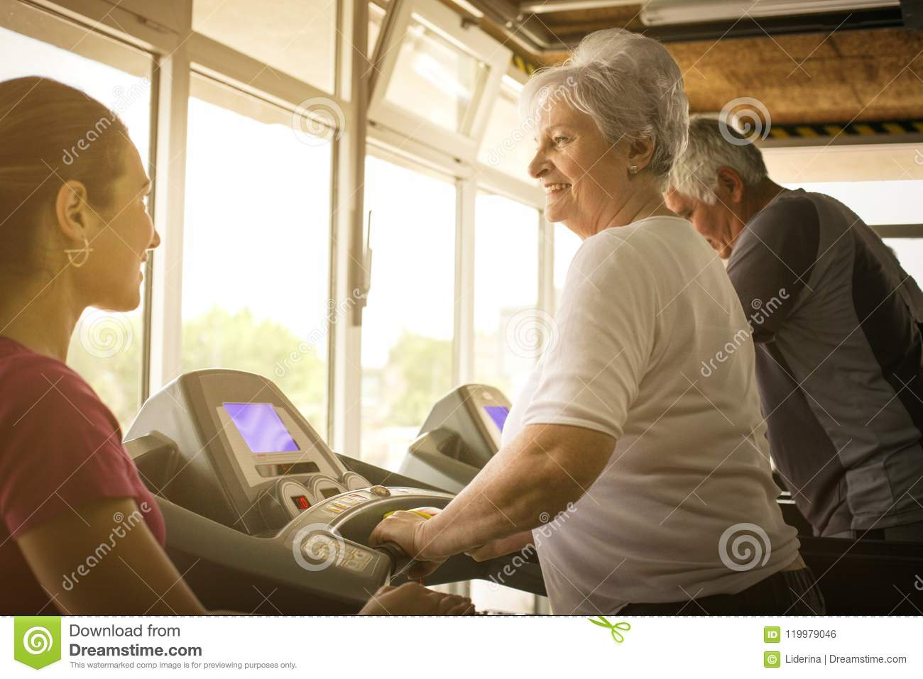 Personal trainer exercise helps elderly couple.