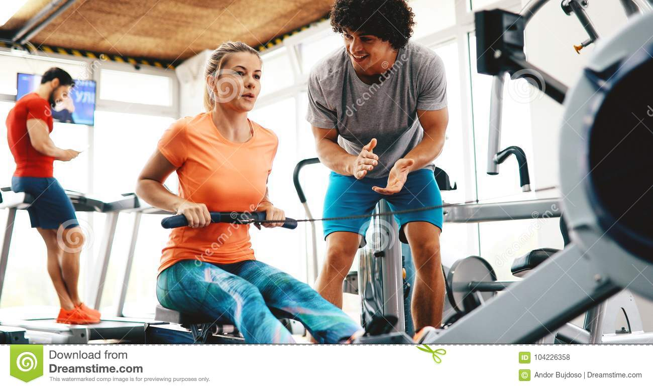 Personal trainer giving instructions in gym stock photo image of