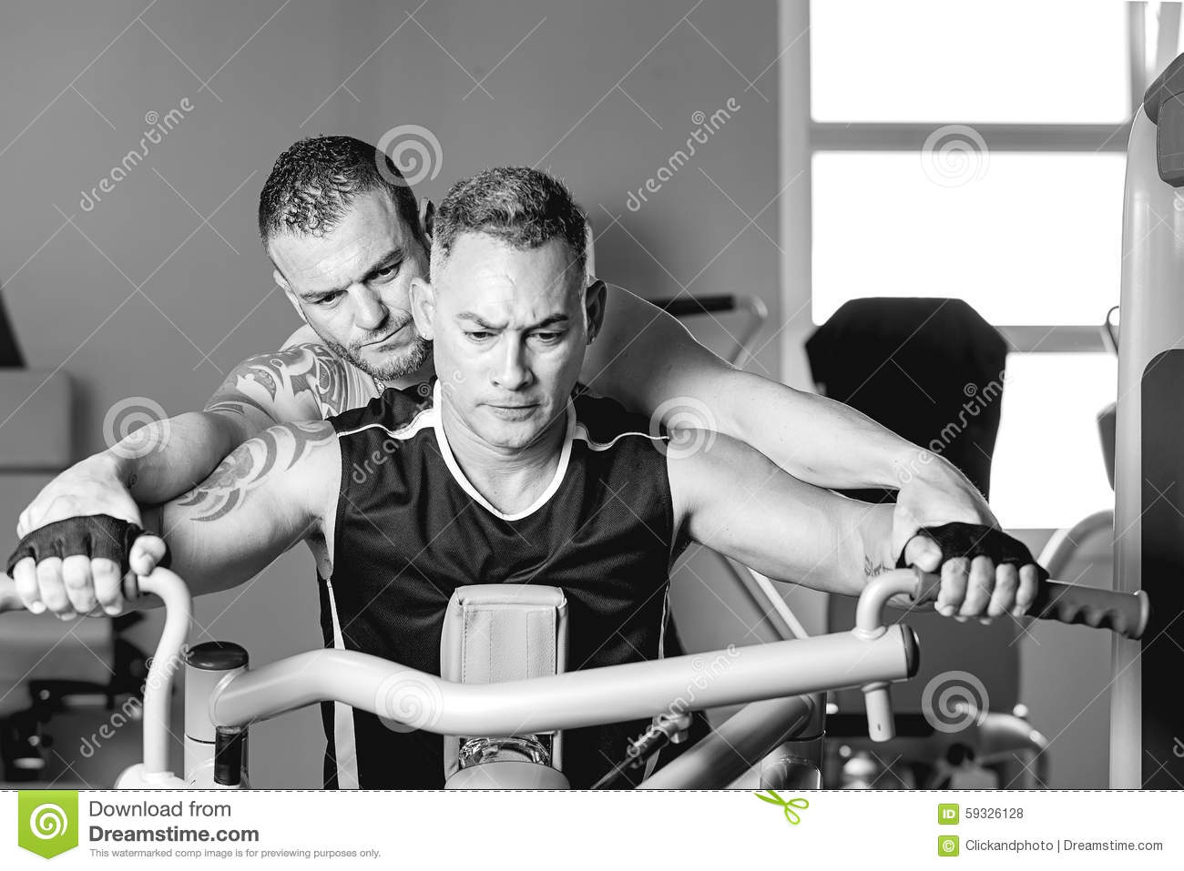 Download Personal Trainer Helping Man With Shoulder Exercise Stock Photo
