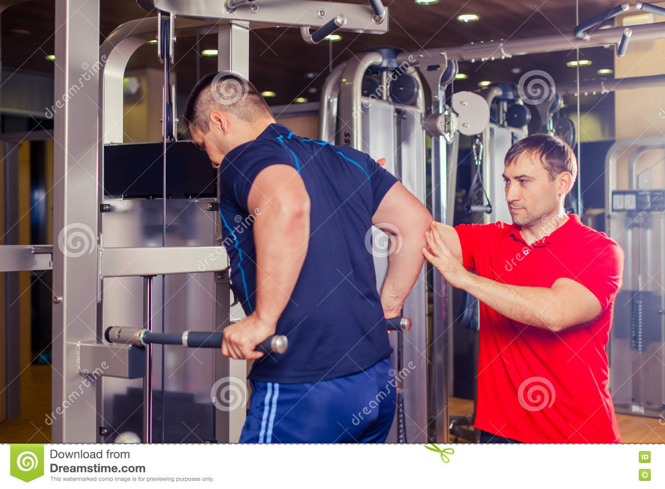 Personal Trainer Helping Men Working Out In Weights Room ...