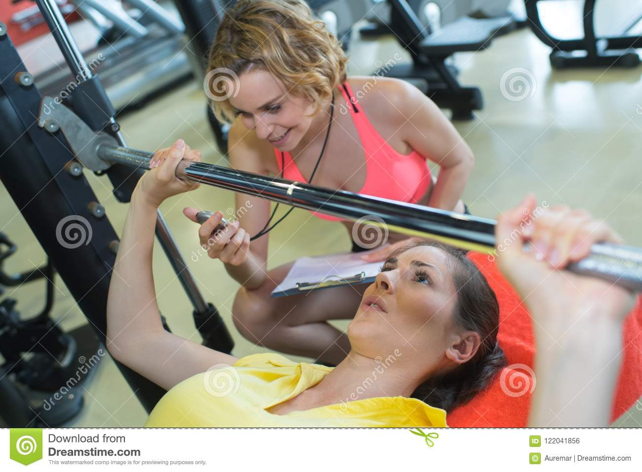 Personal trainer helping woman for correct bench press-training
