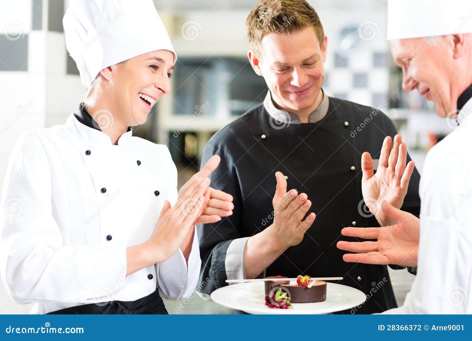 Personas del cocinero en cocina del restaurante con el postre