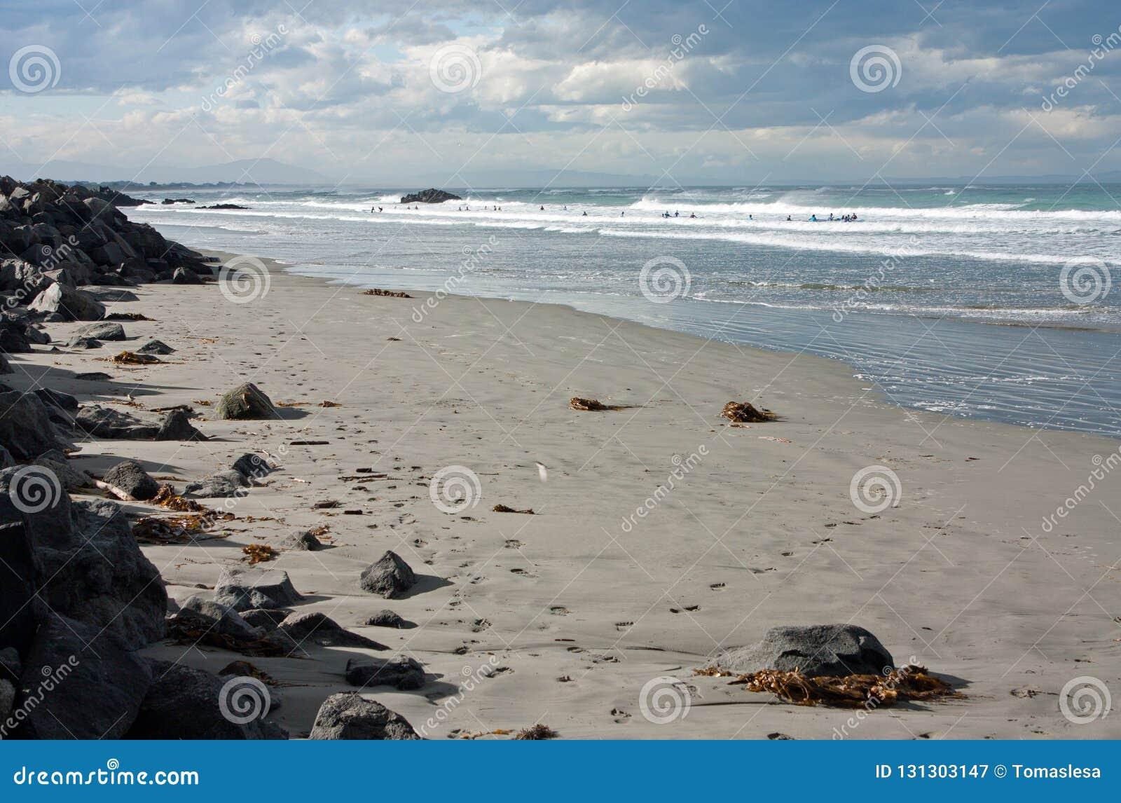 Personas que practica surf en el mar ondulado en Sumner Beach en Christchurch en Nueva Zelanda