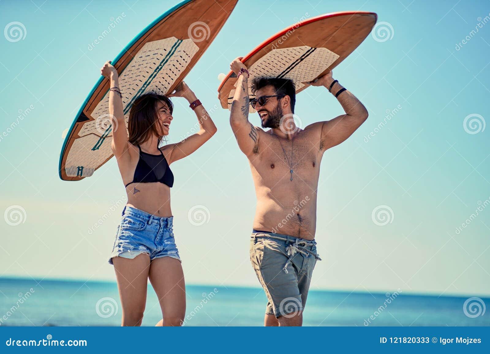 Personas que practica surf en los pares jovenes de la playa de las personas que practica surf que caminan en el bea