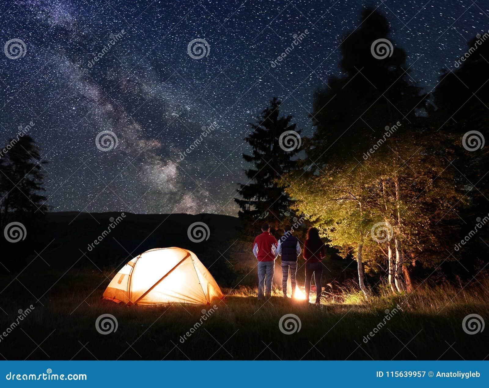 Personblick för bakre sikt tre på den brinnande branden nära tältet och träd under den ovanliga stjärnklara himlen