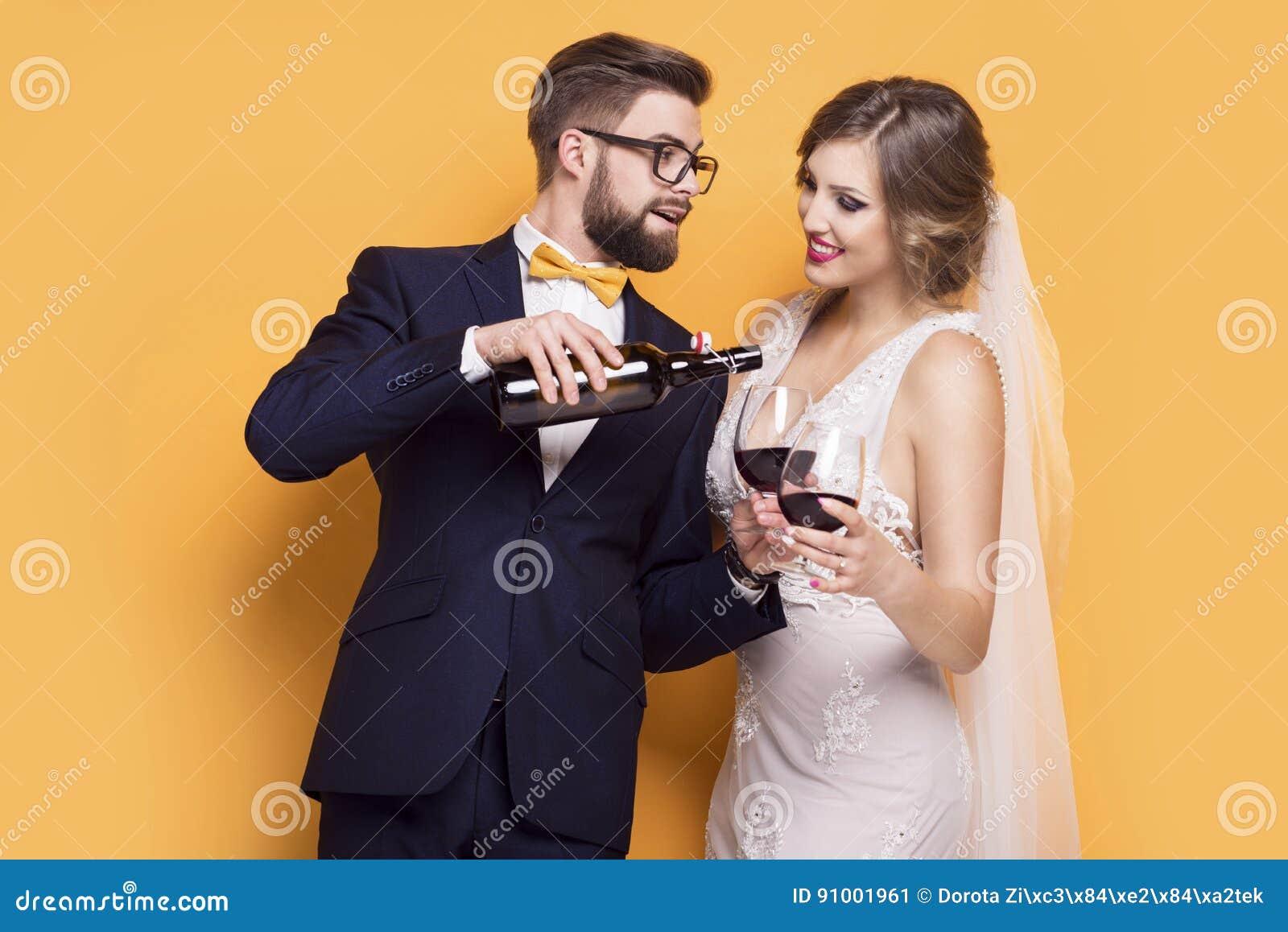 Persone appena sposate che celebrano vino rosso bevente