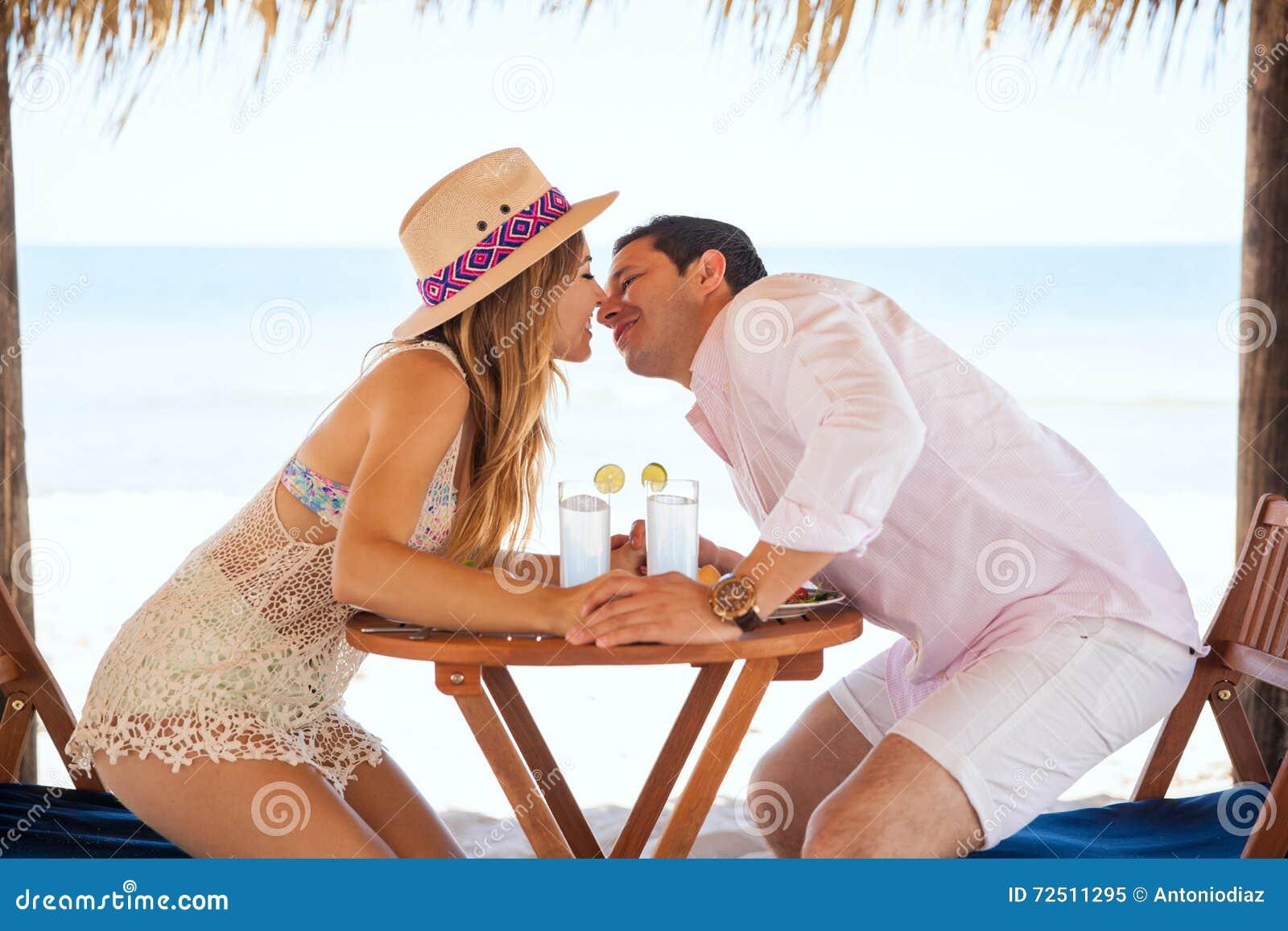 Persone appena sposate circa da baciare alla spiaggia