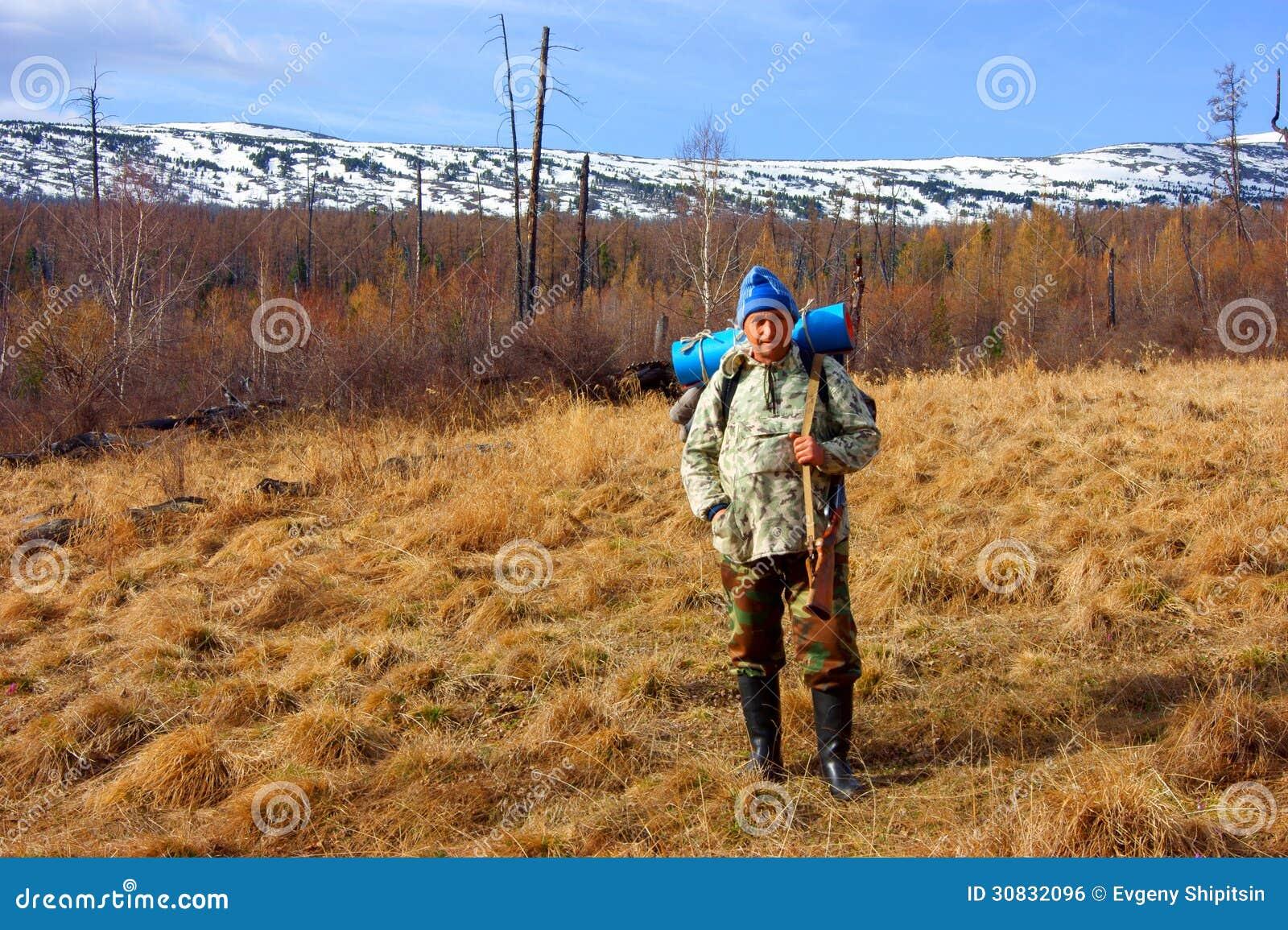 Persone con la rivoltella su fondo delle montagne