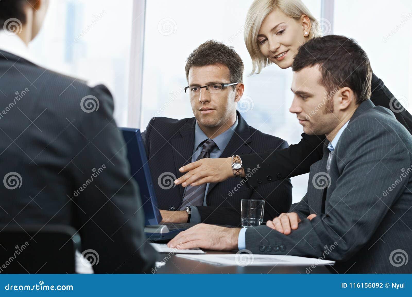 Persone di affari che esaminano computer portatile